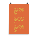 "This is an art print featuring an orange background with bright yellow lowercase type that says, ""Yes, yes, yes."""