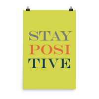 "This is an art print featuring a yellow background with gray, navy, and orange all caps type that says, ""Stay positive."""