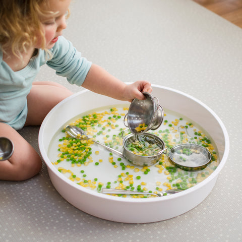 Child scooping peas and sweetcorn in water in the PlayTRAY