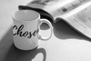 coffee mug with the word chosen written on it in front of a newspaper
