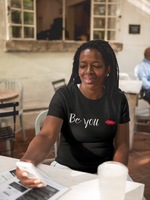 woman wearing a black t shirt wearing with the words Be You written on it.
