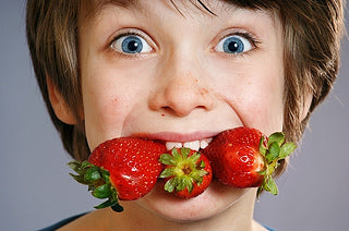 [image: Healthy boy with a mouthful of strawberries. Which are fruits, but are not berries.]