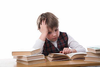 [image: young boy looking overwhelmed, reading books]