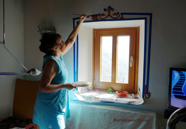 Home owner took this photo of artist Kelly Borsheim painting on his wall in the dining room.