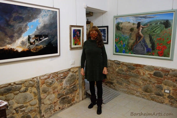 Artist Kelly Borsheim stands between two of her paintings in solo show:  New Years's Eve and Persefone