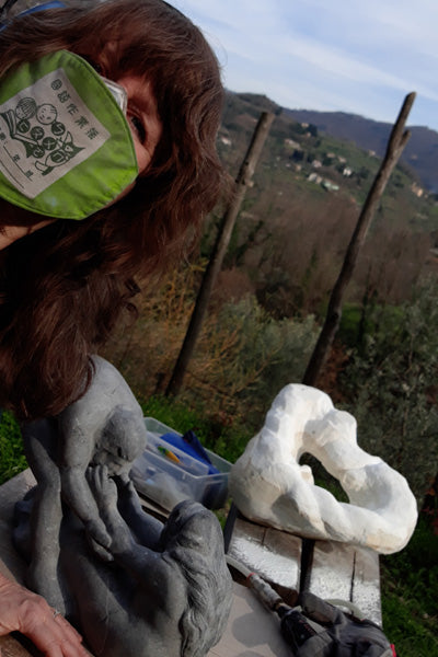 """Another selfie of artist with sculpture.  Here the mostly finished """"Helping Hands"""" in black marble with this white and gold marble portrait."""