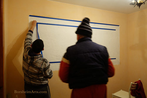 Two men assist in marking straight and horizontal line on the wall for the mural.