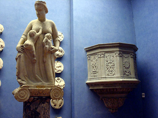 museum quality old statue and pulpit in art collection of the blue walled Bardini Museum in Florence, Italy