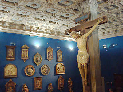 crucifix in a blue room art filled walls and hand carved painted ceiling Bardini Museum Florence Italy