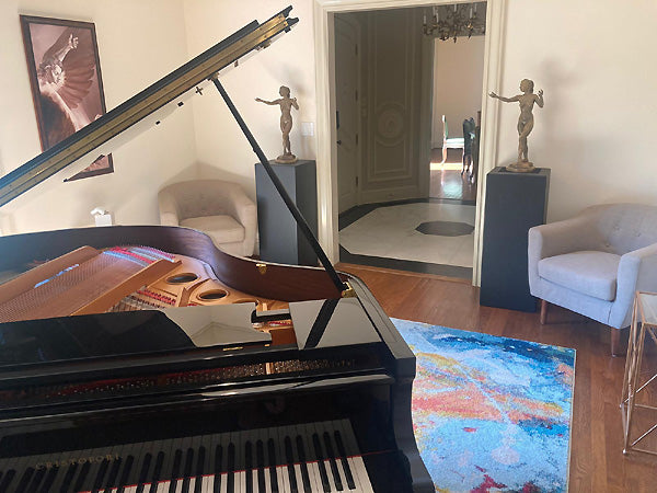 The Triumph of Icarus and bronze Mermaid sculptures in a room with a piano
