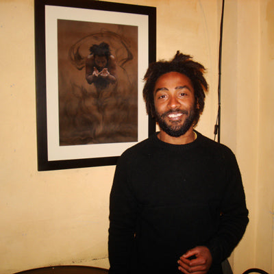 Model Ras Vida poses with the pastel and charcoal drawing of him Il Dono the gift