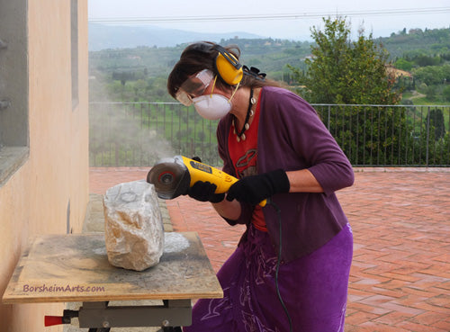 Artist Kelly Borsheim starts on the stone carving When Atlas Tires with a diamond disc cutting into the marble from Carrara, Italy