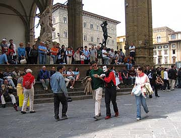 Mime gReY performs in front of the Loggia dei Lanzi in Florence Italy by Pio Fedi sculpture