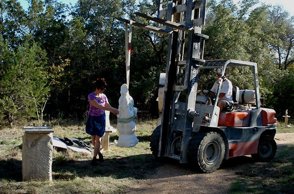 Artist Driving a Fork Lift Moving a Marble Statue into a Sculpture Garden