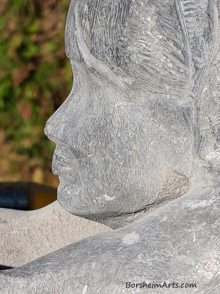 close up of profile of woman's face in stone carving Helping Hands