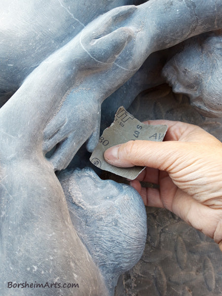 hand using sandpaper to polish stone sculpture