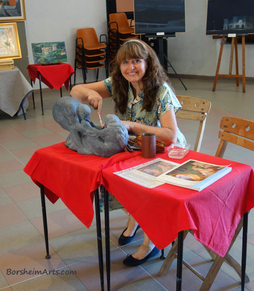 Artist Kelly Borsheim carves stone demonstration at local festival in Italy.