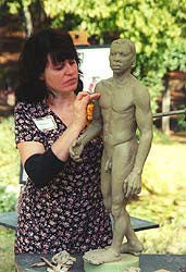 Artist Kelly Borsheim creates a male figure in clay for bronze casting.