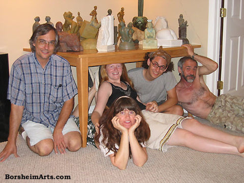 Sculptors and friends and Family pose under a table of small stone carvings statues sculptures