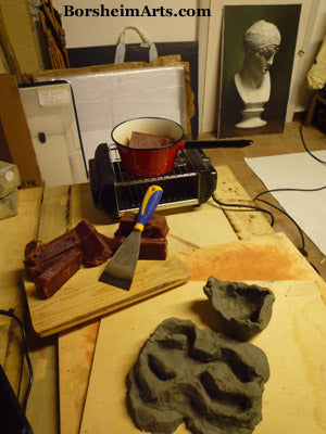 quick temporary molds shaped from clay to pour the beginning wax forms for frogs