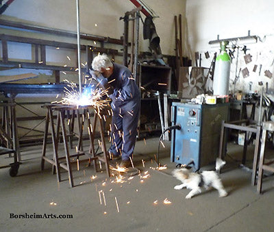 Italian landlord welding sculpture armature while little dog barks at sparks