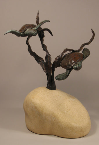 Sea Turtles seem to fly near a kelp plant. sculpture in bronze with limestone curvy hand-carved base that implies the sandy sea floor