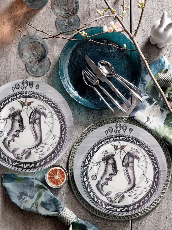 table setting This plate design features and off-center circle border (of shoes shapes) with egg-shaped balloons above the circle on the top section of the plate.  Inside is a fantasy mixture of two shoes, with elements as human hands, fruit, branches, grass, and flowers.  Mostly a black and white design.  Classic, yet Bohemian!