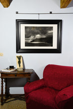 Load image into Gallery viewer, Framed Spotlight charcoal drawing of dramatic skies with sun rays dropping down on cliffs and coastline of Italy, shown here on wall in a small Tuscan living room