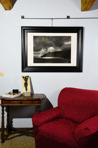 Framed Spotlight charcoal drawing of dramatic skies with sun rays dropping down on cliffs and coastline of Italy, shown here on wall in a small Tuscan living room