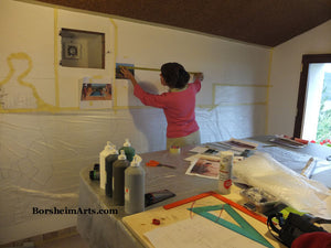 Artist Kelly Borsheim enlarges her mural design on the wall.