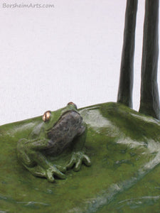 Detail of sitting frog looking up tabletop aquatic bronze sculpture, Cattails and Frog Legs Lily Pad Green Art
