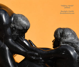 Detail of faces and the hands reaching for the man's face. Black marble figure sculpture detail of Helping Hands