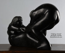 Load image into Gallery viewer, Her face and long hair Helping Hands by Kelly Borsheim Couple Art Carved from a black marble called Bardiglio from Italy, this sculpture depicts a man bending over forward to help a seated woman stand up.  Her hands reach up towards his bearded face, but it is the moment before she is close enough to reach him.