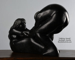 Her face and long hair Helping Hands by Kelly Borsheim Couple Art Carved from a black marble called Bardiglio from Italy, this sculpture depicts a man bending over forward to help a seated woman stand up.  Her hands reach up towards his bearded face, but it is the moment before she is close enough to reach him.