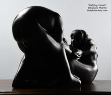Load image into Gallery viewer, Her face looking at the man Helping Hands by Kelly Borsheim Couple Art Carved from a black marble called Bardiglio from Italy, this sculpture depicts a man bending over forward to help a seated woman stand up.  Her hands reach up towards his bearded face, but it is the moment before she is close enough to reach him.