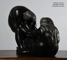 Load image into Gallery viewer, His face, hair and beard and her long hair flowing down the back Helping Hands by Kelly Borsheim Couple Art Carved from a black marble called Bardiglio from Italy, this sculpture depicts a man bending over forward to help a seated woman stand up.  Her hands reach up towards his bearded face, but it is the moment before she is close enough to reach him.