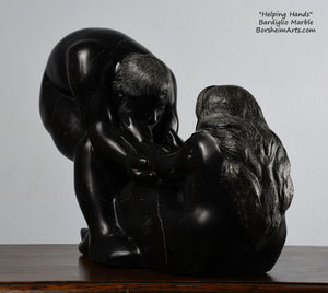 His face, hair and beard and her long hair flowing down the back Helping Hands by Kelly Borsheim Couple Art Carved from a black marble called Bardiglio from Italy, this sculpture depicts a man bending over forward to help a seated woman stand up.  Her hands reach up towards his bearded face, but it is the moment before she is close enough to reach him.