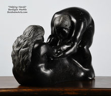 Load image into Gallery viewer, Another angle of the man's face and the woman's long hair Helping Hands by Kelly Borsheim Couple Art Carved from a black marble called Bardiglio from Italy, this sculpture depicts a man bending over forward to help a seated woman stand up.  Her hands reach up towards his bearded face, but it is the moment before she is close enough to reach him.