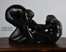 Load image into Gallery viewer, holes under arms in sculpture Helping Hands by Kelly Borsheim Couple Art Carved from a black marble called Bardiglio from Italy, this sculpture depicts a man bending over forward to help a seated woman stand up.  Her hands reach up towards his bearded face, but it is the moment before she is close enough to reach him.