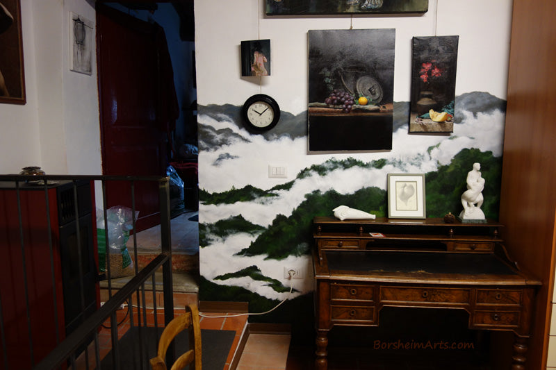 Mural in private home to create a dark background against two white marble sculptures.  Painted clouds floating among green wooded hills in Tuscany, Italy.  by Artist Kelly Borsheim