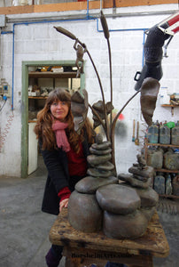 Artist Kelly Borsheim with her sculpture Rock Towers and Frogs Bronze Outdoor Garden Sculpture