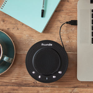The Roundle USB speaker on a desk, with a notepad, computer and coffee cup.
