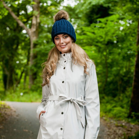 Women Collection at Portwest Ireland | The Outdoor Shop - Model wearing a ladies rain jacket and pom pom beanie hat while walking on an Irish Road in wet weather