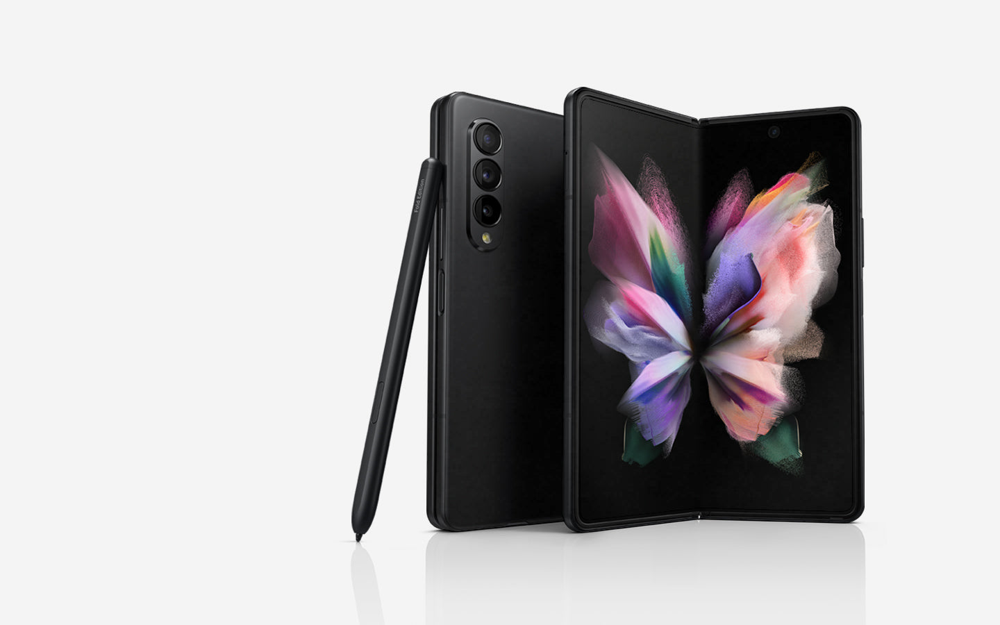 Two Galaxy Z Fold3 5G phones, one seen folded from the Back Cover and one seen unfolded with a colorful wallpaper on the Main Screen. The S Pen Fold Edition leans against the folded phone.