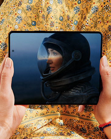 Hands holding Galaxy Z Fold3 5G, unfolded. The Main Screen displays a scene from a game of a woman in a space helmet.