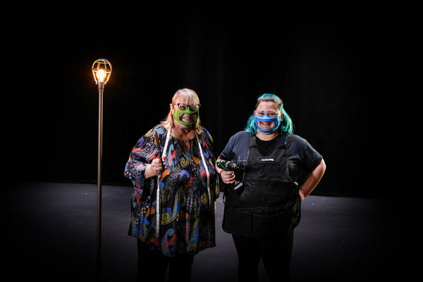 Ingrid Helton, a white woman with blonde hair and Del Hanson, a white person with blue hair stand on a stage in front of a ghost light. Both are wearing a face mask with a plastic window in front of the mouth.