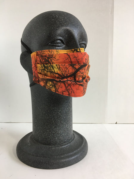 A grey mannequin head wears a face mask with an orange ombre color and brown tree pattern