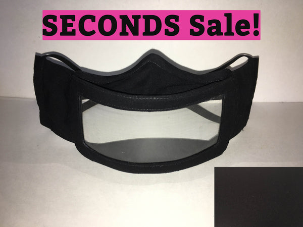 "A black cotton face mask featuring a plastic window over the mouth to help the wearer communicate with people who rely on reading lips. A pink rectangle with the words ""seconds sale!"" is above the mask. A black rectangle is in the bottom right corner."