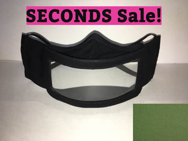 "A black cotton face mask featuring a plastic window over the mouth to help the wearer communicate with people who rely on reading lips. A pink rectangle with the words ""seconds sale!"" is above the mask. A grass green rectangle is in the bottom right corner."