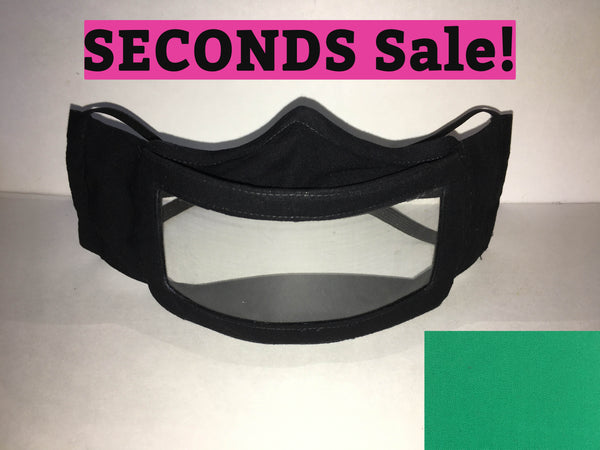 "A black cotton face mask featuring a plastic window over the mouth to help the wearer communicate with people who rely on reading lips. A pink rectangle with the words ""seconds sale!"" is above the mask. A small green rectangle is in the bottom right corner."